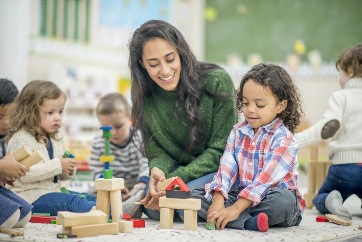 Childcare employee working with children